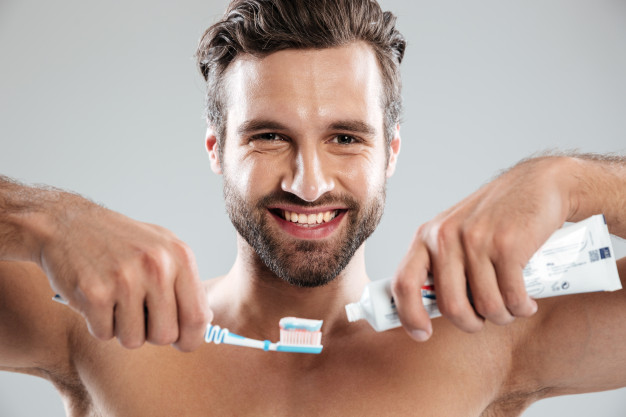 hombre cepillándose los dientes con los mejores productos dentales